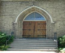 Featured is the double wooden doorway topped by arched gothic transom on the façade.; Kendra Green, 2007