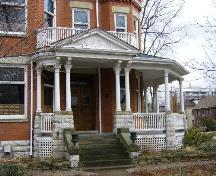 Of note are the front entrance and porch with upper balcony.; Kayla Jonas, 2008.