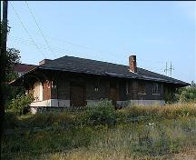 This image presents the building's hipped roof with black asphalt shingles that has a wide overhang supported by decorative brackets resting on granite supports attached to the brick walls.; PNB 2005