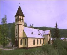 General view of St. Paul's Anglican Church, showing the rectangular massing under a steep gabled roof with truncated transepts, polygonal apse, and  tower with pyramidal, bell-cast roof.; Parks Canada Agency / Agence Parcs Canada.