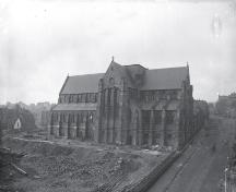 View of the Anglican Cathedral from Cathedral Street, with a view of a corner of the Gower Street Methodist Church on the left, and the old wooden chapel, pre-1892.; Centre for Newfoundland Studies photo 2.02.003