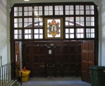 Interior view of the armoury, showing the early heraldic boar crest of the regiment above the door, 2006.; R. Goodspeed, 2006.