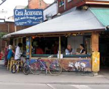 Photo of a cafe at the corner Baldwin Street and Augusta Avenue at the Kensington Market National Historic Site of Canada, 2004.; Agence Parcs Canada / Parks Canada Agency, Michel Pelletier, 2004.