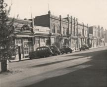 Archival view, from the northwest, of the Forbes Building (right, behind the car), Carberry, 1944; Carberry Plains Archives, 1944