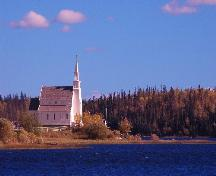 View of the Church in its prominent setting in the northern boreal forest, as seen from the Churchill River.; Government of Saskatchewan, Calvin Fehr, 2004.