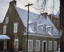 Corner view of Hertel de la Fresnière House at Trois-Rivières Historical Complex, showing the gable roof with dormer windows and twin end-chimneys.; Parks Canada Agency / Agence Parcs Canada
