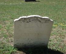 Featured is a headstone with inscription of an early settler interred at the cemetery.; Kendra Green, 2007.
