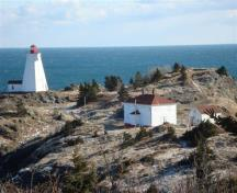 Image of the Swallowtail Light Keeper's House in winter, 2010, showing the windows boarded up.  Swallowtail Lighthouse is on the left.; Grand Manan Historical Society