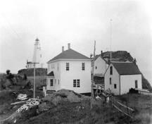 This historic image shows the Swallowtail Light Keeper's House, constructed in 1958, with its outbuildings and a boathouse. ; Laurie Murison