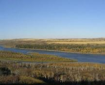 View of island on far side of river (fur trade remains are in stand of tall, dark spruce trees), 2004.; Government of Saskatchewan, Marvin Thomas, 2004