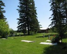 View of cemetery with Metis cabin in background, 2009.; Ross Herrington, 2009.