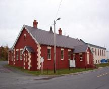 Constructed in 1876, Heart's Content Cable Station, with its distinctly Gothic bargeboard, reflected the very popular features of English gatehouses and stables of the time. The 1876 original (red) and 1918 extension (white) are shown in this photo.; Government of Newfoundland and Labrador 2005