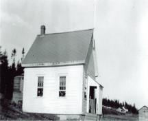 Image of the Deep Cove School taken around 1943 with children hanging out the windows.; Grand Manan Archives P8 photo collection