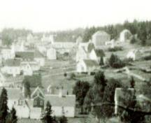 This image shows the Seal Cove School after the 1935 extension. The image is dated 'post-WWII'. The school is the long white building in the top centre of the photo.  ; Grand Manan Archives