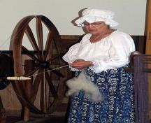 Image showing Betty Adams working the spinning wheel; Village of Dorchester