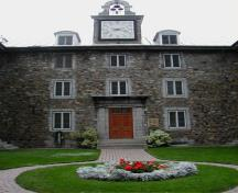 Detailed view of Saint-Sulpice Seminary, showing the main door and the clock with mounted bells.; Parks Canada Agency / Agence Parcs Canada.