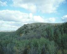 Distance view of the outcrop where the petroglyphs are located, 1993.; Government of Saskatchewan, 1993.
