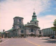 General view of Notre-Dame Roman Catholic Cathedral, showing a richly detailed Neoclassical facade flanked by two towers of different age and design.; Parks Canada Agency/Agence Parcs Canada
