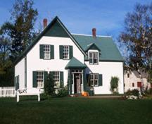 View of the main entrance of Green Gables House, showing the one-and-a-half storey, L-shaped massing topped by a gable roof with a dormer window on the front façade and the small vestibule entrance, 2000.; Parks Canada Agency / Agence Parcs Canada, J. Sylvester, 2000.