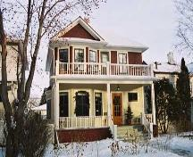 This image illustrates the two storey south and west wood-clad facades with hipped-roof and front gable over two-storey bay window, central chimney, full-width main floor veranda and open balcony above and side bay window with hipped-roof. (March 2004); City of Edmonton, 2004