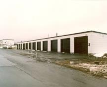 Corner view of Building 501, showing the white painted shingles on the exterior wood-framed walls, 1986.; Public Works and Government Services Canada / Travaux publics et Services gouvernementaux Canada , 1986.