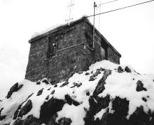 Side view of Sulphur Mountain Weather Station, showing its simple, one-storey massing with a hipped roof, 1986.; Environment Canada, Parks Canada Agency, Western Regional Office, 1986 / Environnement Canada, Agence Parcs Canada, Bureau de la région de l'Ouest, 1986.