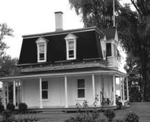 Side view of the Superintendent's Residence, showing the two-storey massing with a four-sided mansard roof with overhanging eaves and gabled dormers, 1972.; Parks Canada Agency / Agence Parcs Canada, 1972.
