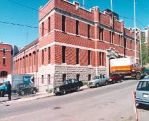 Corner view of the Armoury, showing the horizontal bands of sleek stone work, the split-faced stone foundation wall and the bartizan above the entrance which indicate the military function of the building, 1994.; Parks Canada Agency / Agence Parcs Canada, 1994.