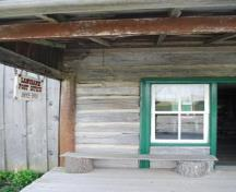 Post Office's front entrance, surrounded by original log; board and batten siding visible on left; Photographs taken by Dana Johnson, May 4th, 2010, with permission of  the Oil Museum of Canada