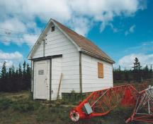 View of the entrance of the Ice House, showing the simple massing composed of one storey with a gable roof covered with asphalt shingles, 1995.; Department of Public Works / Ministère des Travaux publics, 1995.