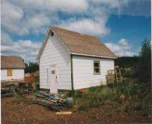 Corner view of the Quarters/Storage Building 2, showing the wood-frame construction and white asbestos siding, 1995.; Public Works and Government Services Canada / Travaux publics et Services gouvernementaux Canada, 1995.