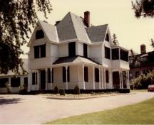 View of the main façade of Heritage House (Building 54), showing the large scale and massing of the house, which consists of a two-and-a-half storey structure with a verandah around two sides and a hip and gable roof, 1982.; Agence Parcs Canada / Parks Canada Agency, Janet Wright and Monique Trepanier, 1982.