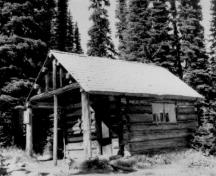 Corner view of the Warden's Cabin at Eva Lake, showing its walls, raised in horizontal logs, dove-tailed at the corners and pierced by a plank door and two multi-paned fixed sash windows, 1986.; Parks Canada Agency / Agence Parcs Canada, 1986.