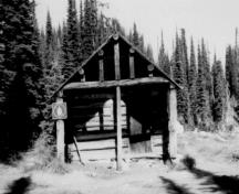 Front elevation of the Warden's Cabin at Eva Lake, showing its front gable end encased in a porch framed by extended roof purlins and supporting vertical log posts, 1986.; Parks Canada Agency / Agence Parcs Canada, 1986.