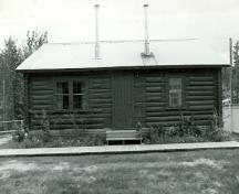Front elevation of the N.W.M.P Married Officers' Quarters, showing the log construction of peeled local spruce logs, sawn on three sides and lapped at the corners, 1987.; Agence Parcs Canada / Parks Canada Agency, 1987.