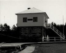View of the Blockhouse, showing the square, two-storey massing with pyramidal roof, 1989.; Agence Parcs Canada / Parks Canada Agency, 1989.
