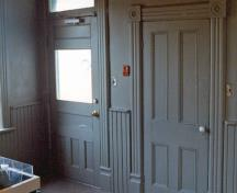 Interior view of the Lockmaster's House, showing the woodwork and the waist-high wooden wainscotting, 1989.; Parks Canada Agency / Agence Parcs Canada, 1989.