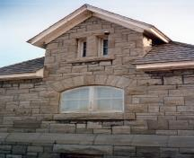 Side view of the Maintenance Building, showing the stone walls, built up in irregularly coursed rough-cut limestone, 1988.; Parks Canada Agency / Agence Parcs Canada, 1988.