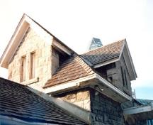 Detail view of the Maintenance Building, showing the hip and cross gable roof, 1988.; Parks Canada Agency / Agence Parcs Canada, 1988.