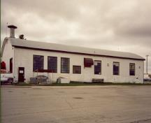 General view of Hangar 13, showing its varying fenestration and one-storey rectangular massing with a low bowed roof, 1992.; Department of National Defence / ministère de la Défense nationale, 1992.