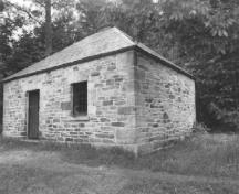 Corner view of the Blacksmith's Shop, showing the exterior walls, constructed of rough-faced masonry blocks, the limited number of windows and the door, 1989.; Public Works and Government Services Canada / Travaux publics et Services gouvernementaux Canada, 1989.