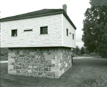 Corner view of the Blockhouse, showing the square, two-storey massing with pyramidal roof and chimney, 1989.; Department of Public Works / Ministère des Travaux publics, 1989.