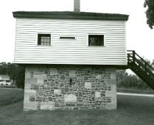 Side elevation of the Blockhouse, showing the ground floor of stone masonry and the timber framed upper storey covered with clapboard, 1989.; Department of Public Works / Ministère des Travaux publics, 1989.