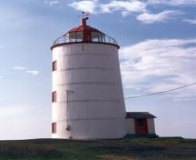 Side view of the Lighttower, showing its short, circular, slightly tapered masonry, and the vertical white wood boards, girded by five metal hoops, 1989.; Ministère des Affaires culturelles du Quebec / Quebec Ministry of Cultural Affairs, 1989.