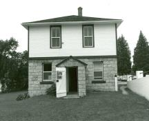 View of the main entrance of the Lower Brewers Defensible Lockmaster's House, showing the symmetrical elevations with regular placement of the windows and doors, 1989.; Department of Public Works / Ministère des Travaux publics, 1989.