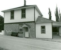 Side view of the Lower Brewers Defensible Lockmaster's House, showing the thick ground floor wall constructed of evenly coursed limestone masonry with infilled loopholes, and the frame second floor clad in clapboard, 1989.; Department of Public Works / Ministère des Travaux publics, 1989.