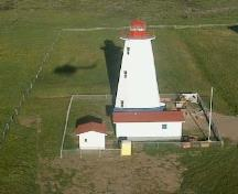 General view of Cape Anguille Light Tower, showing the tapered, octagonal form of the light tower consisting of a tall concrete shaft surmounted by a small lantern, 2000.; Department of Fisheries and Oceans / Ministères des Pêches et Océans, 2000.
