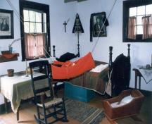Interior view of Louis Riel House, showing an interpretation of the house in mourning in 1886, 1999.; Parks Canada Agency / Agence Parcs Canada, 1999.