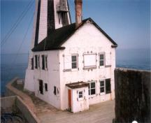 Gannet Rock Lightstation, showing its reinforced concrete walls, windows equipped with wooden shutters, and direct access to the tower from each level of the dwelling, 1999.; Canadian Coast Guard / Garde côtière canadienne, 1999.