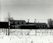 View of the Woodworking Shop, showing the exterior form of the building, which speaks to the transitory nature of many of the activities it accommodated and its workshop function, 1989.; Agence Parcs Canada / Parks Canada Agency, 1989.